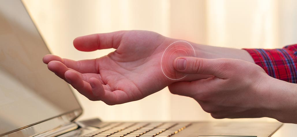 person holding wrist at computer due to carpal tunnel syndrome