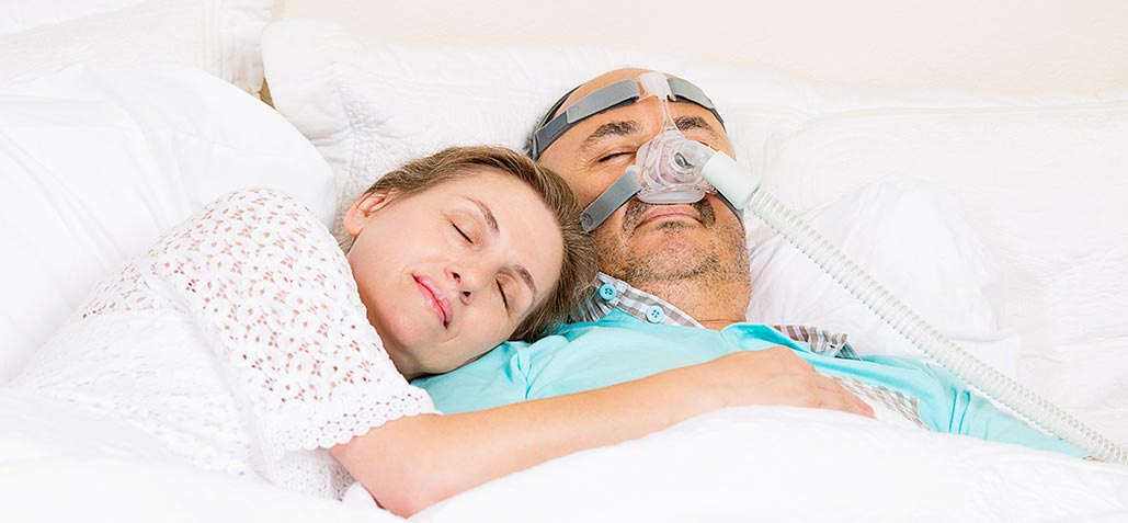 man sleeping with cpap machine next to wife