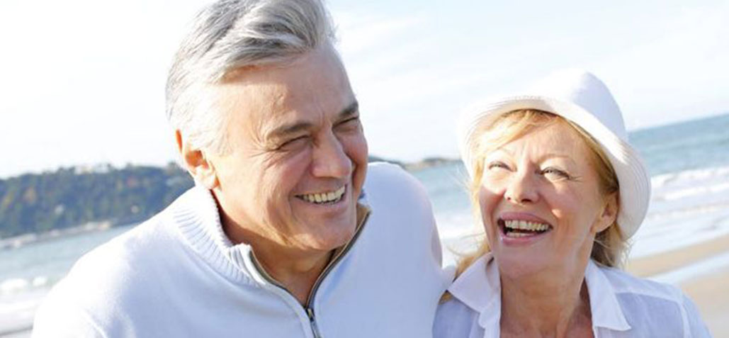 older couple laughing at beach